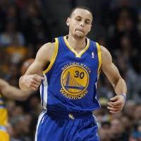 Photo - Golden State Warriors guad Stephen Curry reacts after hitting a basket in the fourth quarter of the Warriors' 131-117 victory over the Denver Nuggets in Game 2 of the teams' NBA first-round playoff series in Denver on Tuesday, April 23, 2013. (AP Photo/David Zalubowski)