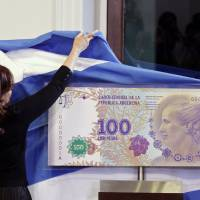 Photo - FILE - In this July 25, 2012 photo, Argentina's President Cristina Fernandez unveils an archetype of the new 100 Argentine pesos bill bearing the profile of former late first lady Maria Eva Duarte de Peron, better known as