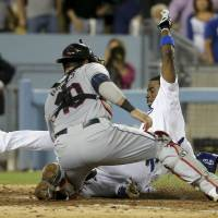 Photo - Los Angeles Dodgers' Dee Gordon, right, is tagged out at home by Cleveland Indians catcher Yan Gomes after Adrian Gonzalez lined into a triple play during the fourth inning of a baseball game in Los Angeles, Tuesday, July 1, 2014. (AP Photo/Chris Carlson)