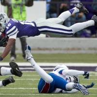 Photo - Kansas State's Tyler Lockett (16) is knocked into the air by Kansas' Josh Ford (8) while returning a kick during the first half of an NCAA college football game in Manhattan, Kan., Saturday, Oct. 6, 2012. (AP Photo/Orlin Wagner) ORG XMIT: KSOW104