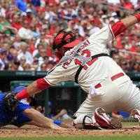 Photo - Chicago Cubs' Chris Valaika, left, is safe at home as St. Louis Cardinals catcher A.J. Pierzynski attempts the tag during the second inning in the first baseball game of a doubleheader, Saturday, Aug. 30, 2014, in St. Louis. (AP Photo/Jeff Roberson)