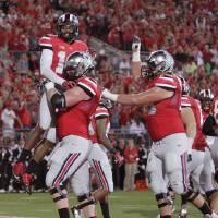 Photo - Ohio State wide receiver Corey Brown, top, celebrates his touchdown against Wisconsin with teammates during the second quarter of an NCAA college football game Saturday, Sept. 28, 2013, in Columbus, Ohio. (AP Photo/Jay LaPrete)