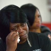 Photo - Nichole Mitchell wipes away tears during the sermon at a youth service at the St. Paul Missionary Baptist Church in Sanford, Fla., Sunday, July 14, 2013.  Many in the congregation wore shirts in support of Trayvon Martin following the acquittal oif George Zimmerman, who had been charged in the 2012 shooting death of  Martin.(AP Photo/Phelan M. Ebenhack)