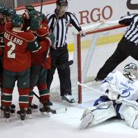 Photo - Minnesota Wild players congratulate right wing Nino Niederreiter as Tampa Bay Lightning goalie Ben Bishop, right, looks away after Niederreiter's power play goal during the first period of an NHL hockey game in St. Paul, Minn., Tuesday, Feb. 4, 2014. (AP Photo/Ann Heisenfelt)