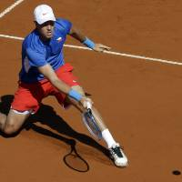 Photo -   Czech Republic's Tomas Berdych returns the ball to Argentina's Carlos Berlocq during the Davis Cup semifinals tennis match in Buenos Aires, Argentina on Sunday, Sept. 16, 2012. (AP Photo/Natacha Pisarenko)