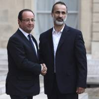 Photo -   French President Francois Hollande, left, welcomes head of the new Syrian National Coalition for Opposition and Revolutionary Forces Mouaz al-Khatib, prior to a meeting, at the Elysee Palace, in Paris, Saturday, Nov. 17, 2012. France has taken a leading role among Western countries in supporting Syria's rebels. On Tuesday, it became the first Western nation to formally recognize Syria's newly formed opposition coalition as the sole legitimate representative of the Syrian people. (AP Photo/Thibault Camus)