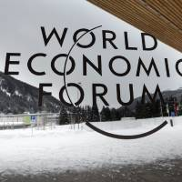 Photo - A man walks outside the main entrance of the Congress Center, on the eve of the opening of the 43rd Annual Meeting of the World Economic Forum, WEF, in Davos, Switzerland, Tuesday, Jan. 22, 2013. The overarching theme of the meeting, which will take place from 23 to 27 January, is