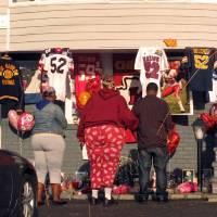 Photo - People stand by a small shrine outside the Long Island home of Kansas City Chiefs linebacker Jovan Belcher, Monday, Dec. 3, 2012, in West Babylon, N.Y. People living at and visiting the home stopped and recited a prayer at the shrine on Monday. On Saturday, Belcher killed his girlfriend and himself in Kansas City, Mo. (AP Photo/Frank Eltman)