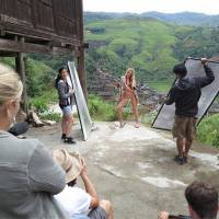 Photo - This Sept. 10, 2012 image released by Sports Illustrated shows a model being photographed on location in Guilin, China, for the 2013 Sports Illustrated Swimsuit issue. Sports Illustrated took its models to all seven continents for the first time. The around-the-globe effort will be chronicled by the Travel Channel in a special on Feb. 17. Sports Illustrated said Tuesday it's the first to do a fashion shoot in Antarctica, where temperatures were subfreezing.  Among the locations featured are Namibia, China, Australia and Easter Island, one of the most remote places on Earth. Swimsuit magazine editor MJ Day says it took seven months to complete. Sports Illustrated will reveal its cover Monday. It can be a star-making opportunity. Last year's cover model was Kate Upton. The magazine hits newsstands Feb. 12. (AP Photo/Valery Gherman for Sports Illustrated) FOR NORTH AMERICAN USE ONLY IN CONJUNCTION WITH THE PROMOTION OF THE TRAVEL CHANNEL SPECIAL UNTIL FEB. 28, 2013.