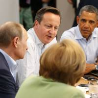 Photo - G8 leaders from left, German Chancellor Angela Merkel, Russian President Vladimir Putin, Britain's Prime Minister David Cameron and US President Barack Obama attend a working session during the G-8 summit at the Lough Erne golf resort in Enniskillen, Northern Ireland on Tuesday, June 18, 2013. (AP Photo/Yves Herman, Pool)