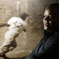 Photo - Former Chicago White Sox player Frank Thomas visits a Jackie Robinson exhibit during his orientation visit at the Baseball Hall of Fame on Monday, March 3, 2014, in Cooperstown, N.Y. Thomas will be inducted to the hall in July. (AP Photo/Mike Groll)