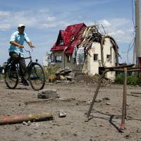 Photo - A man rides a bike past a house damaged during fighting, outside the city of Slovyansk, Donetsk Region, eastern Ukraine Thursday, July 10, 2014. In the past two weeks, Ukrainian government troops have halved the amount of territory held by the rebels. Now they are vowing a blockade of Donetsk. In another sign of deteriorating morale among rebels, several dozen militia fighters in Donetsk abandoned their weapons and fatigues Thursday, telling their superiors they were returning home. (AP Photo/Dmitry Lovetsky)