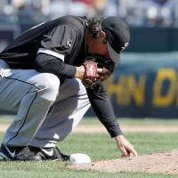 Photo - Chicago White Sox relief pitcher Scott Downs draws in the dirt behind the mound during the eighth inning of a baseball game against the Kansas City Royals at Kauffman Stadium in Kansas City, Mo., Saturday, April 5, 2014. The Royals won 4-3. (AP Photo/Orlin Wagner)