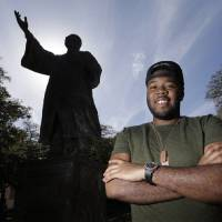 Photo - In this March 5, 2013 photo, University of Texas senior Bradley Poole poses for a photo on campus near the Martin Luther King Jr. statue in Austin, Texas. Poole, an advertising major, became president of the school's Black Student Alliance, seeking camaraderie after noticing he often was the only African-American in his classes. In two pivotal legal cases, one on affirmative action and another on voting rights, a divided U.S. Supreme Court may be poised in the coming weeks to rule that racism is largely a relic of America's past. The question is apt as the nation nears a demographic tipping point, when non-whites become the country's majority for the first time. (AP Photo/Eric Gay)