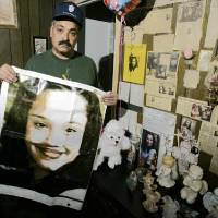 Photo - FILE - In this Friday, March 3, 2004 file photos shows Felix DeJesus, holding a banner showing his daughter's photograph, standing by a memorial in his living room in Cleveland. Cleveland police say two women who went missing as teenagers about a decade ago have been found alive in a residential area about two miles south of downtown. Cheering crowds gathered Monday night on the street near the home where police say Amanda Berry, Gina DeJesus and a third woman were found earlier in the day. The identity of the third woman hasn't been confirmed. (AP Photo/Tony Dejak, File)