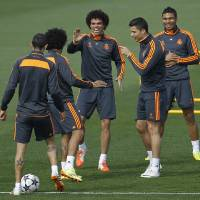 Photo - Real's Cristiano Ronaldo, second right, gestures next to Pepe, center, and teammates during a training session in Madrid, Spain, Tuesday, April 22, 2014. Real Madrid will face Bayern Munich in a first leg semifinal Champions League soccer match on Wednesday. (AP Photo/Gabriel Pecot)