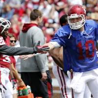 Photo - Roy Finch (22) and Blake Bell (10) shake hands before the annual Spring Football Game at Gaylord Family-Oklahoma Memorial Stadium in Norman, Okla., on Saturday, April 13, 2013. Photo by Steve Sisney, The Oklahoman