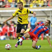 Photo - Dortmund's Ciro Immobile, left,  and Munich's Philipp Lahm vie for the ball with during the German soccer Super Cup match between Borussia Dortmund and Bayern Munich in Dortmund, Germany, Wednesday, Aug. 13, 2014. (AP Photo/Sascha Schuermann)