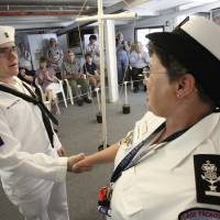Photo - Sea Scout Matt Lebo, left, shakes hands with Kenna Green, the skipper of Sea Scouts Ship 131. Photos by DAVID MCDANIEL, THE OKLAHOMAN