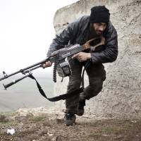 Photo - In this Monday, Dec. 17, 2012 photo, a Free Syrian Army fighter takes cover during fighting with the Syrian Army in Azaz, Syria. (AP Photo/Virginie Nguyen Huang)