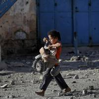 Photo - A Palestinian girl walks with a toy that she salvaged from debris of the el-Yazje apartment building which was destroyed following an overnight Israeli missile strike in Gaza City, Thursday, July 17, 2014. The Israeli military says it has struck 37 targets in Gaza ahead of a five-hour humanitarian cease-fire meant to allow civilians to stock up after 10 days of fighting. The Gaza Interior Ministry says four people were killed and that a 75-year-old woman died of wounds from the day before. The Israeli army says Hamas fired 11 rockets at Israel early Thursday. Palestinian health officials say that in total, at least 225 Palestinians have been killed. On the Israeli side, one man was killed since July 8. (AP Photo/Lefteris Pitarakis)