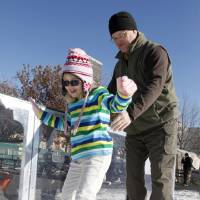 Photo - Left: John Hubert helps his  daughter, Isabel, 7, learn to skate Saturday at the Devon Ice Rink.