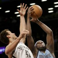 Photo - Memphis Grizzlies' Zach Randolph, right, fights for a rebound with Brooklyn Nets' Kris Humphries during the first half of the NBA basketball game at the Barclays Center Sunday, Feb. 24, 2013 in New York.  (AP Photo/Seth Wenig)