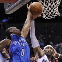 Photo - New Jersey Nets guard Vince Carter, right, fight for a rebound with Oklahoma City Thunder guard Russell Westbrook during the fourth quarter of an NBA basketball game Monday night, Jan. 12, 2009 in East Rutherford, N.J. The Nets beat the Thunder 103-99 in overtime.  (AP Photo/Bill Kostroun) ORG XMIT: ERA105