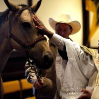 Photo - The Rev. Joseph Alsay blesses Sissy the horse as Michael West looks on during a  Blessing of the Animals service in honor of St. Francis of Assisi's feast day at St. Augustine of Canterbury Episcopal Church in Oklahoma City. PHOTOS BY SARAH PHIPPS, THE OKLAHOMAN
