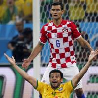 Photo - In this Thursday, June 12, 2014 photo, Brazil's Fred raises his arms after a penalty was called against Croatia's Dejan Lovren, top, by referee Yuichi Nishimura, from Japan, during the group A World Cup soccer match between Brazil and Croatia in the opening game of the tournament at the Itaquerao Stadium in Sao Paulo, Brazil. Brazil was issued a penalty kick following the play leading to a goal by Neymar helping Brazil to a 3-1 victory. (AP Photo/Frank Augstein)