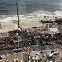Photo - This aerial photo shows aftermath of a massive fire that burned a large portion of the Seaside Park boardwalk, Friday, Sept. 13, 2013, in Seaside Park, N.J. The fire, which apparently started Thursday in an ice cream shop and spread several blocks, hit the recently repaired boardwalk, which was damaged last year by Superstorm Sandy. (AP Photo/The Asbury Park Press, Bob Bielk)
