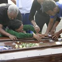 Photo - A survivor cries on the casket of her sister who died when their boat capsized off in the Canal of Sicily before it is embarked on a Italian Navy ship at the Lampedusa island harbor, Saturday, Oct. 12, 2013. A fishing boat packed with 500 African migrants capsized on Thursday Oct. 3, 2013 off the shores of the island of Lampedusa, causing more than 300 dead. The enormous scale of the tragedy, which could become the largest death toll in a migrant shipwreck in the Mediterranean on record, has created momentum for a comprehensive European Union immigration policy to cope with the tens of thousands fleeing misery and strife in Africa and the Middle East. (AP Photo/Mauro Buccarello)