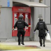 Photo -   Los Angeles Police bomb squad members check for explosive devices outside a Bank of America branch in Los Angeles Wednesday, Sept. 5, 2012. Authorities say two gunmen kidnapped a bank manager, held her overnight and strapped a device to her stomach before robbing a Bank of America. The woman then had employees take money from the bank and put it outside. The suspects remain at large. (AP Photo/Damian Dovarganes)
