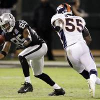 Photo - Oakland Raiders wide receiver Darrius Heyward-Bey (85) catches a pass as Denver Broncos linebacker D.J. Williams (55) watches during the second quarter of an NFL football game in Oakland, Calif., Thursday, Dec. 6, 2012. (AP Photo/Ben Margot)