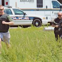 Photo - Drug Task Force Detective Josh Talbott, left, and Jonesboro Police Department Patrolman First Class Duane Busby run across a field adjacent to Moore Road while responding to a Saturday, May 3, 2014 shooting in Jonesboro, Ark. A gunman shot six people at an Arkansas home Saturday, killing a man and a teenager and critically wounding two boys, before fatally shooting a worker at a nearby business, police said. (AP Photo/The Jonesboro Sun, Sarah Morris)