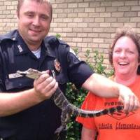 Photo -  Officer Bobby Qualls holds an alligator found loose in a residential neighborhood in Sallisaw by Sheila Johnson. (Sequoyah County Times photo)