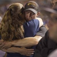 Photo - Firefighter Brendan McDonough embraces a mourner near the end of a candlelight vigil in Prescott, Ariz. on Tuesday, July 2, 2013. McDonough was the sole survivor of the 20-man Granite Mountain Hotshot Crew after an out-of-control blaze killed the 19 on Sunday near Yarnell, Ariz. (AP Photo/Julie Jacobson)