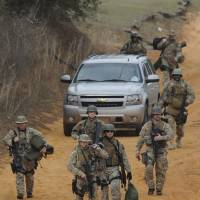 Photo - Heavily armed men come back down the hill from the direction of the suspect's home at the Dale County hostage scene near Midland City, Ala. on Wednesday Jan. 30, 2013. Police SWAT teams and hostage negotiators were locked in a standoff Wednesday with a gunman authorities say intercepted a school bus, killed the driver, snatched a 6-year-old boy and retreated into a bunker at his home. (AP Photo/Montgomery Advertiser, Mickey Welsh)    NO SALES