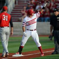 Photo - Indiana's Kyle Schwarber acknowledges the dugout and crowd after his triple during an NCAA college regional baseball game against Youngstown State in Bloomington, Ind. Friday, May 30, 2014. Youngstown State's Matt Sullivan covers third base. (AP Photo/The Herald-Times, Chris Howell)