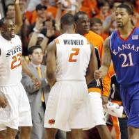 Photo - From left, OSU's James Anderson (23), Obi Muonelo (2) and Torin Walker (10) celebrate in front of KU's Markieff Morris (21) in the first half during the men's college basketball game between the University of Kansas (KU) and Oklahoma State University (OSU) at Gallagher-Iba Arena in Stillwater, Okla., Saturday, Feb. 27, 2010. Photo by Nate Billings, The Oklahoman ORG XMIT: KOD