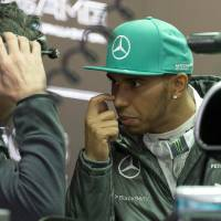 Photo - Mercedes driver Lewis Hamilton of Britain chats with his crew inside the garage during the practice session ahead of Sunday's Chinese Formula One Grand Prix at Shanghai International Circuit in Shanghai, China Friday, April 18, 2014. (AP Photo/Andy Wong)