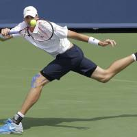 Photo - John Isner returns a serve against Andy Murray, from Great Britain, during a match at the Western & Southern Open tennis tournament, Thursday, Aug. 14, 2014, in Mason, Ohio. (AP Photo/Al Behrman)