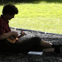 Photo -  Austin Pendley-Griffin finds a shady spot to play his ukulele at E.C. Hafer Park during the Fourth of July holiday weekend. PHOTO BY PAUL HELLSTERN, THE OKLAHOMAN   PAUL HELLSTERN -