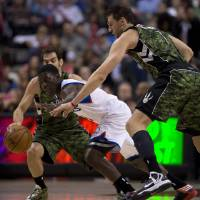 Photo -   Toronto Raptors forward Andrea Bargnani, right, and Philadelphia 76ers guard Jrue Holiday chase a loose ball during first-half NBA basketball action action in Toronto, Saturday, Nov. 10, 2012. (AP Photo/The Canadian Press, Frank Gunn)