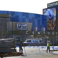 Photo - Workers with American Fence remove the fence from around the Century theater in Aurora, Colo., on Thursday, Jan. 17, 2013.  The Colorado movie theater where a gunman killed 12 people and wounded dozens of others reopens Thursday with a private ceremony for victims, first responders and officials.   Theater owner Cinemark plans to temporarily reopen the entire 16-screen complex in Aurora to the public on Friday, then permanently on Jan. 25. Aurora's mayor, Steve Hogan, has said residents overwhelmingly support reclaiming what he calls