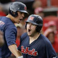 Photo - Mississippi's Sikes Orvis (24) is greeted at the dugout by Colby Bortles after hitting a solo home run in the fourth inning of an NCAA college baseball tournament super regional game against Louisiana Lafayette in Lafayette, La., Monday, June 9, 2014. (AP Photo/Gerald Herbert)