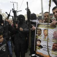 Photo - A man holds a poster showing imprisoned Palestinians as he is surrounded by armed militants in in the Balata refugee camp in the West Bank town of Nablus during a rally in support of Palestinian prisoners Friday,  Feb. 22, 2013. Israel holds a few thousand Palestinians on charges ranging from rock throwing to deadly attacks. (AP Photo/Nasser Ishtayeh)