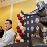 Photo - CORRECTS YEAR - Texas A&M freshman quarterback Johnny Manziel answer questions during a Cotton Bowl press conference, with a Heisman Trophy at side, at the Omni Mandalay hotel, Tuesday, Jan. 1, 2013, in Irving, Texas. Texas A&M plays Oklahoma on Jan. 4 in the Cotton Bowl in Arlington, Texas. (AP Photo/Brandon Wade) ORG XMIT: TXBW103
