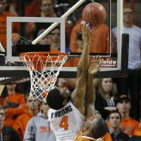 Photo - Oklahoma State's Brian Williams (4) blocks the shot of Texas' Kendal Yancy during an NCAA college basketball game between the Oklahoma State Cowboys (OSU) and the University of Texas Longhorns at Gallagher-Iba Arena in Stillwater, Okla., Wednesday, Jan. 8, 2014. Oklahoma State won 87-74. Photo by Bryan Terry, The Oklahoman