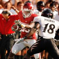 Photo - Ryan Broyles runs after a catch and a Cincinnati coach reacts in the background during the college football game between the University of Oklahoma (OU) and Cincinnati at Gaylord Family -- Oklahoma Memorial Stadium in Norman, Okla., Saturday, September 6, 2008.  Defending is Cedric Tolbert (18).  BY STEVE SISNEY, THE OKLAHOMAN ORG XMIT: KOD